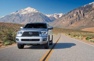 2020 Toyota Sequoia going down the road with mountains in the background