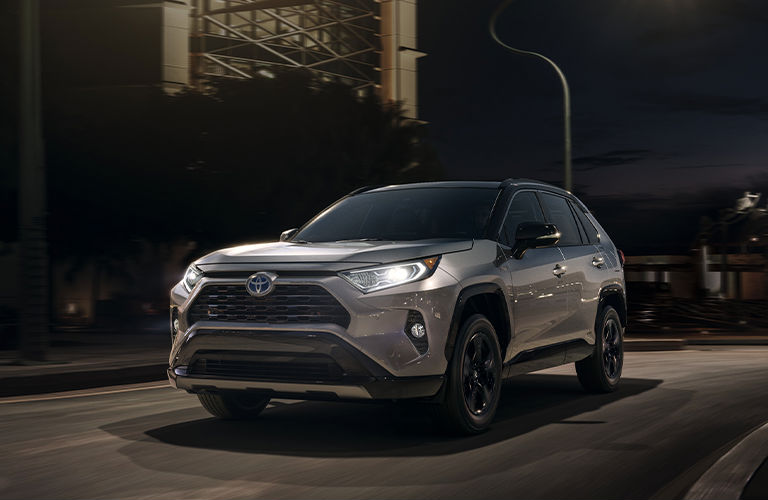 2020 Toyota RAV4 Hybrid going down the street at night