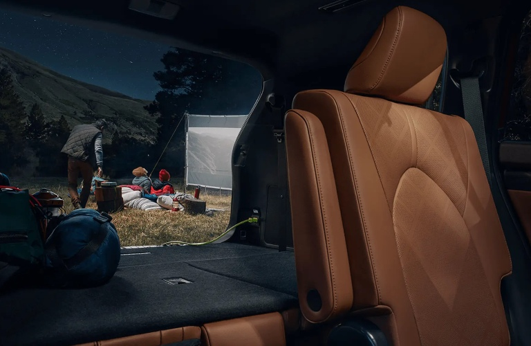 Back seats inside of the 2021 Toyota Highlander Hybrid folded down showing a family outside
