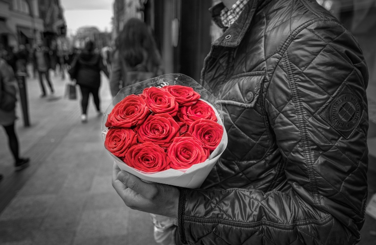 Black and white photo of man holding roses and roses are in color