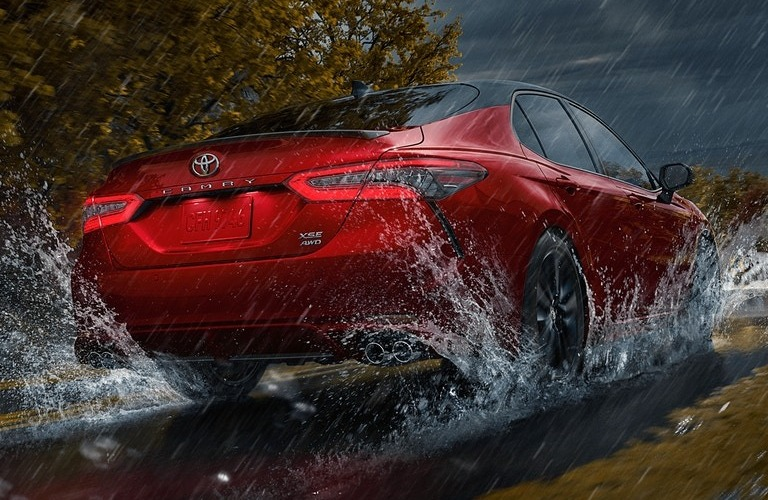 2021 Toyota Camry driving through a puddle in the rain