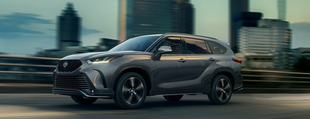 2021 Toyota Highlander going down the highway with large buildings in the background