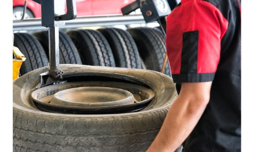 dirty tire getting changed and balanced by technician