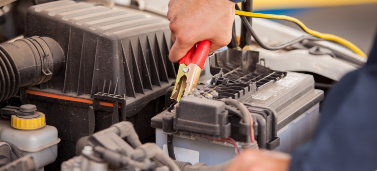 tech working on a car battery