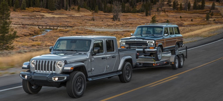 2020 Jeep Gladiator silver towing a classic Jeep on a trailer