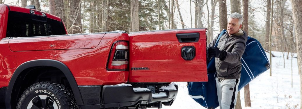 2019 RAM 1500 Rebel red with a multi-function tailgate and a man loading the back