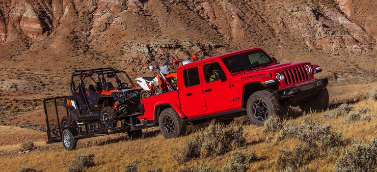 2020 Jeep Gladiator red side view towing an ATV with a motorcycle in the bed