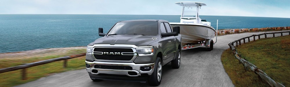 Front view of 2020 RAM 1500 towing boat on waterfront road