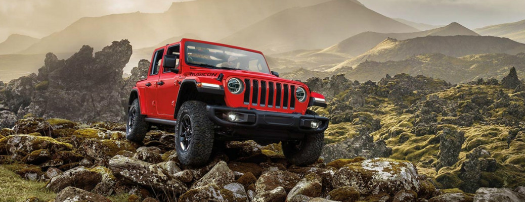 Red 2020 Jeep Wrangler driving on rocky terrain