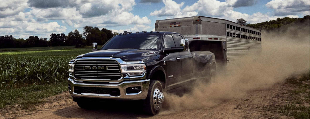 Dark blue 2020 Ram 3500 Heavy Duty towing a trailer on a dirt road