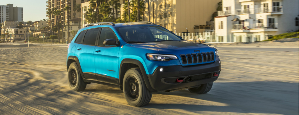 Blue 2020 Jeep Cherokee driving on a beach
