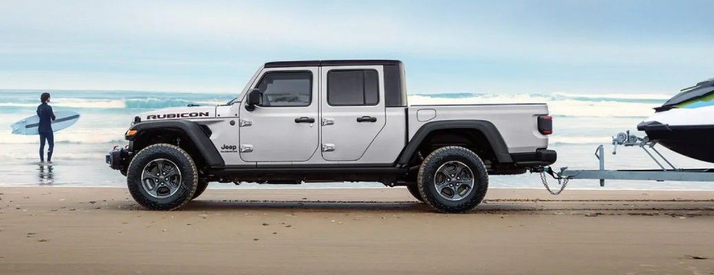 2021 Jeep Gladiator Rubicon exterior side shot parked on a beach while towing a boat as a surfer stands in the water