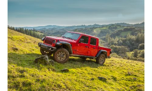 2021 Jeep Gladiator Rubicon exterior shot in Firecracker Red parked on a grassy hill under the sun