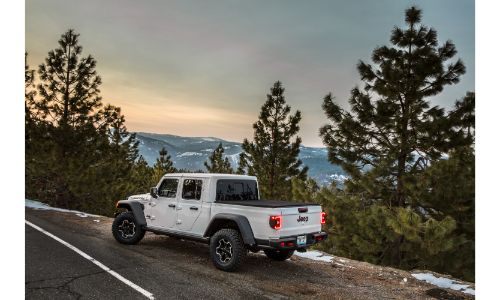 2021 Jeep Gladiator Rubicon exterior shot in Bright White parked on the side of a country forest highway at sunset
