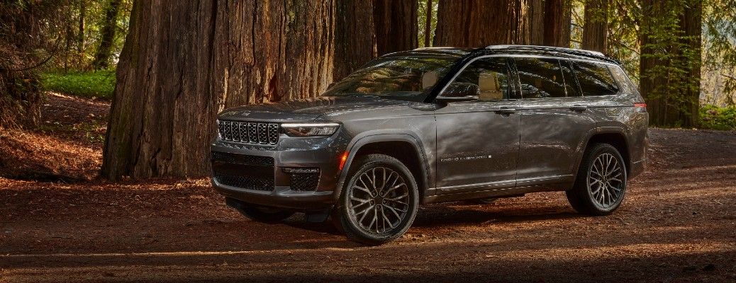 2021 Jeep Grand Cherokee L exterior shot with gray paint color parked in a forest clearing surrounded by trees