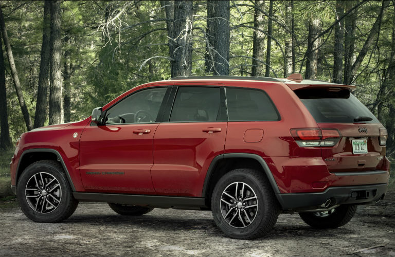 A red-colored 2021 Jeep Grand Cherokee parked outside near trees