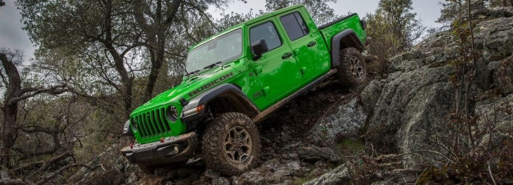 A Gecko Green colored Jeep Gladiator Rubicon 4X4 pickup truck scaling down a rocky terrain