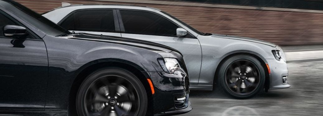 Two 2021 Chrysler 300 sedans racing with each other under rain