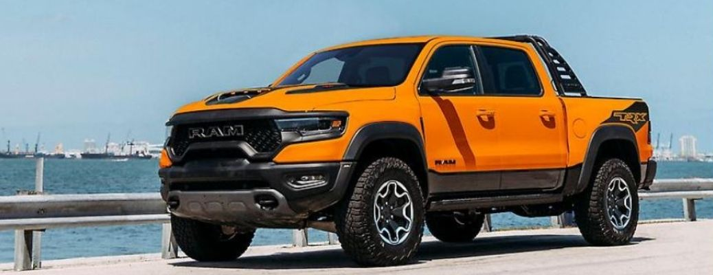 A 2022 Ram 1500 TRX Ignition Edition in Ignition Orange exterior paint parked on a street facing the sea