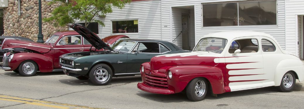 3 classic cars lined up on the street