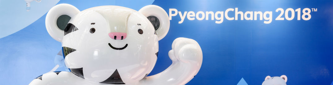 "Ceramic bear waving in front of a banner with ""PyeongChang 2018"" written on it"
