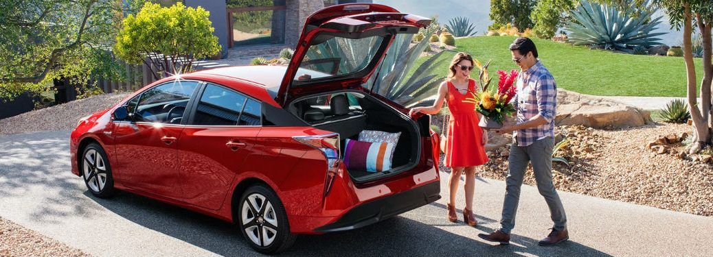 Happy couple loading cargo into the rear of a red 2018 Toyota Prius