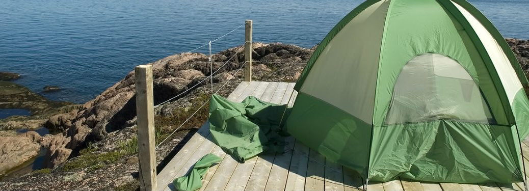 backpacking tent on wooden platform on hill overlooking water