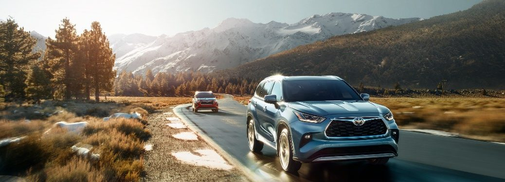 Two 2021 Toyota Highlander vehicles driving on a road