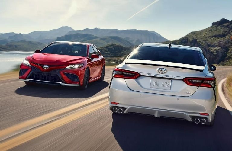 Two 2022 Toyota Camry crossing each other on the road showing front and back exterior
