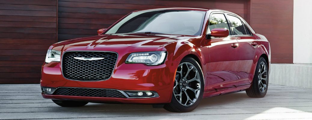 2019 Chrysler 300 exterior shot with velvet red paint color parked on a stone planked patio with a red wood garage behind it