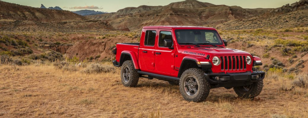 2019 Jeep Gladiator exterior shot with firecracker red paint color parked in a field of shriveled grass in the wilderness