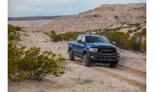 2019 Ram Heavy Duty Power Wagon exterior shot with blue paint color driving down a sandy dirt road