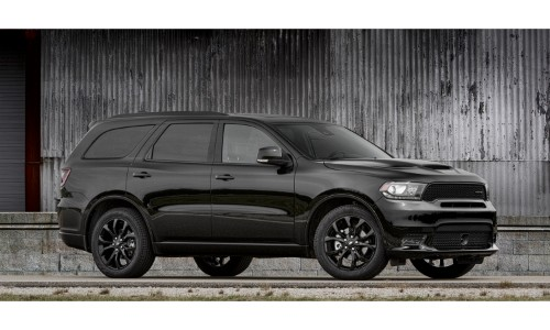 2019 Dodge Durango GT exterior side shot with black paint color parked outside a warehouse with warped metal siding