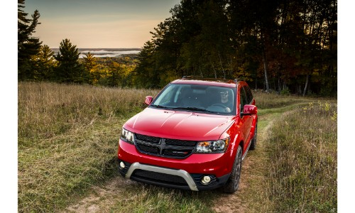 2019 Dodge Journey Crossroad exterior shot with red paint color driving through a field of high grass right outside a hill forest