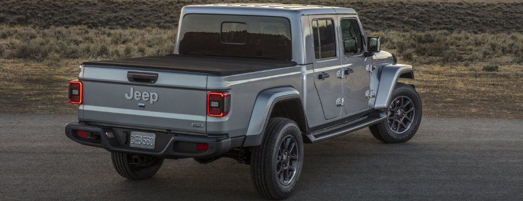 2020 Jeep Gladiator pickup truck exterior rear shot with billet silver metallic paint color parked outside in the field as the sun sets
