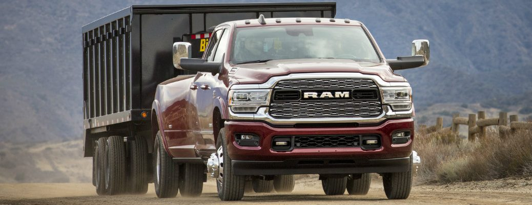 2019 Ram 3500 Heavy Duty Limited Crew Cab exterior front shot with red paint color as it tows a large container on a dirt road