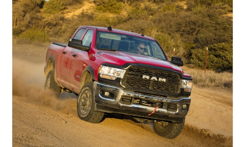 2019 Ram 2500 Heavy Duty Power Wagon Crew cab exterior shot with red paint color driving over a dirt hill