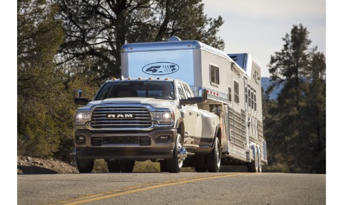 2019 Ram 3500 Heavy Duty Longhorn Mega cab exterior shot with white paint color pulling a large trailer RV down a highway