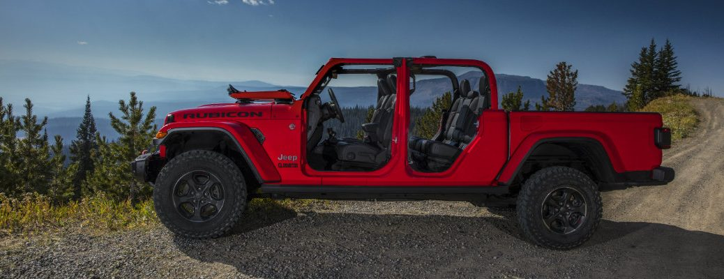 2020 Jeep Gladiator Rubicon exterior side shot with red paint and doors removed parked at the side of a gravel path on a mountain forest