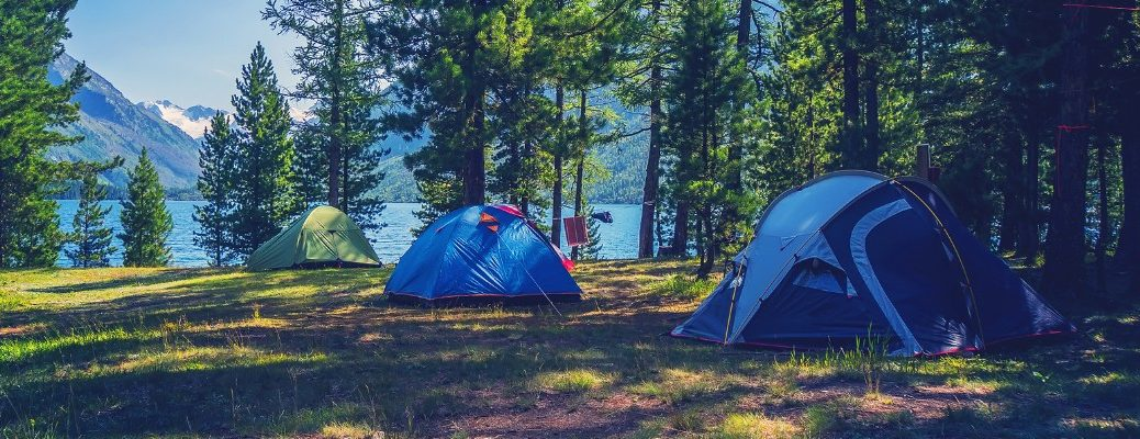 a line of camping test in an open field of grass surrounded by forest trees and near a lake with a mountain range