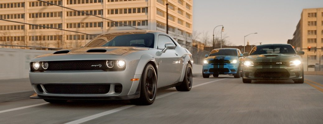 Dodge Challenger, Charger, and Durango SRT models driving through a city as the sun sets and LED headlights turn on to promote Dodge Power Dollars program