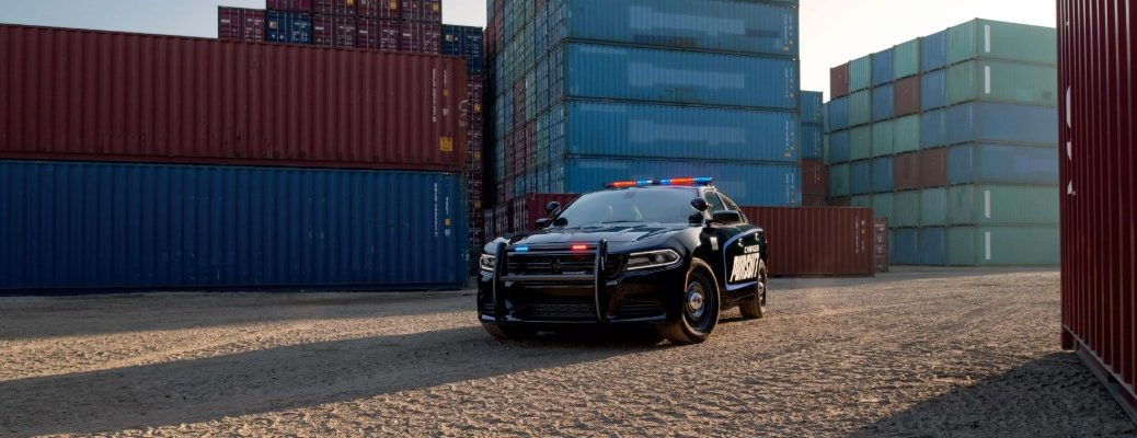 2020 Dodge Charger Pursuit law enforcement police sedan exterior shot with police color branding, emergency chase lights parked in a storage container lot