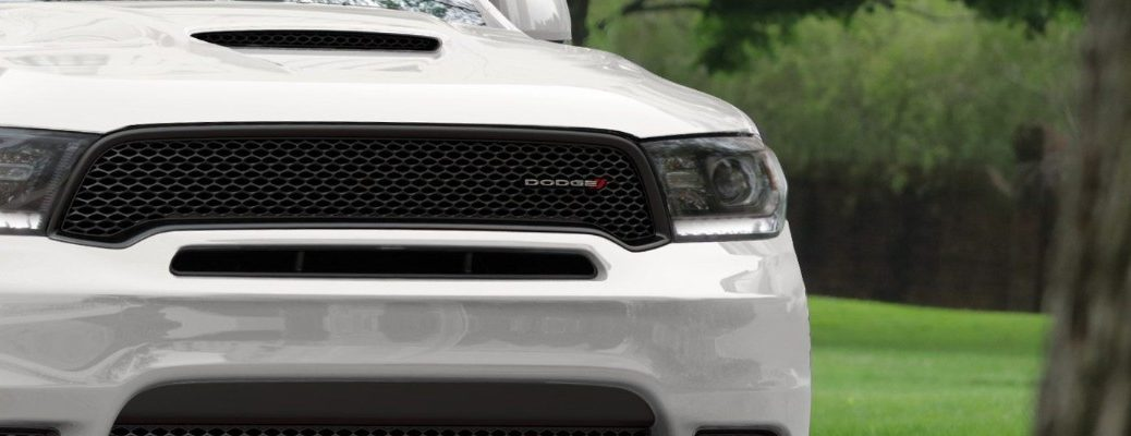 2020 Dodge Durango exterior close up on air vent hood and grille with Dodge make badge and white coat paint color