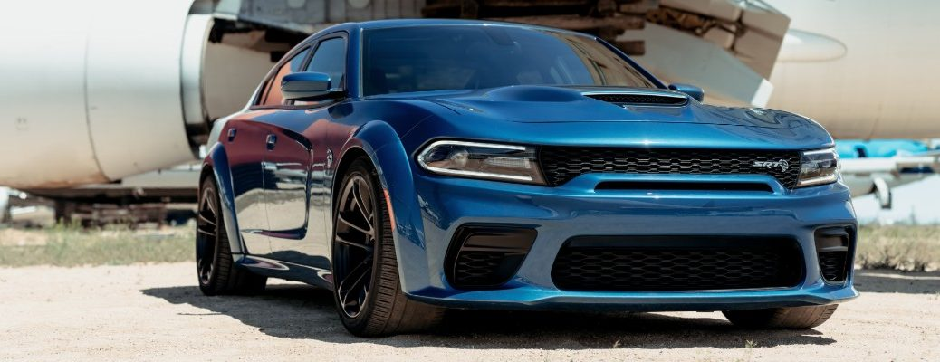 2020 Dodge Charger SRT Hellcat Widebody exterior shot with blue paint color parked outside of an airplane engine in a desert beach of sand