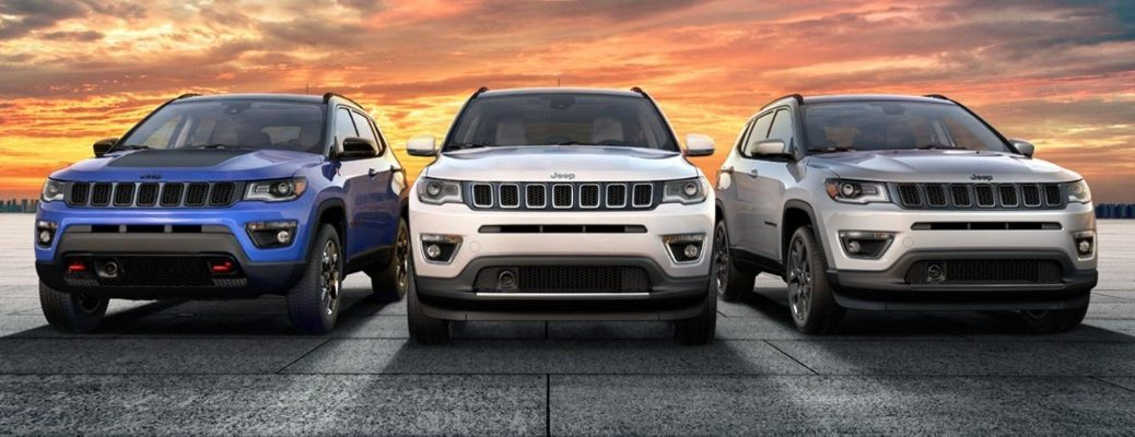 2020 Jeep Compass models in blue, white, and gray paint colors parked on a stone plaza with a orange sunset sky background