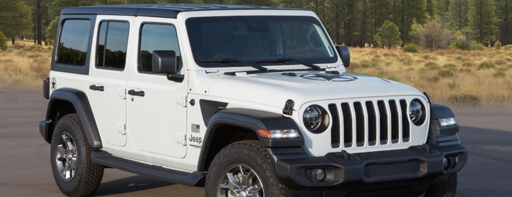 2020 Jeep Wrangler Freedom Special Edition model exterior shot in white parked near forests and mountain ranges