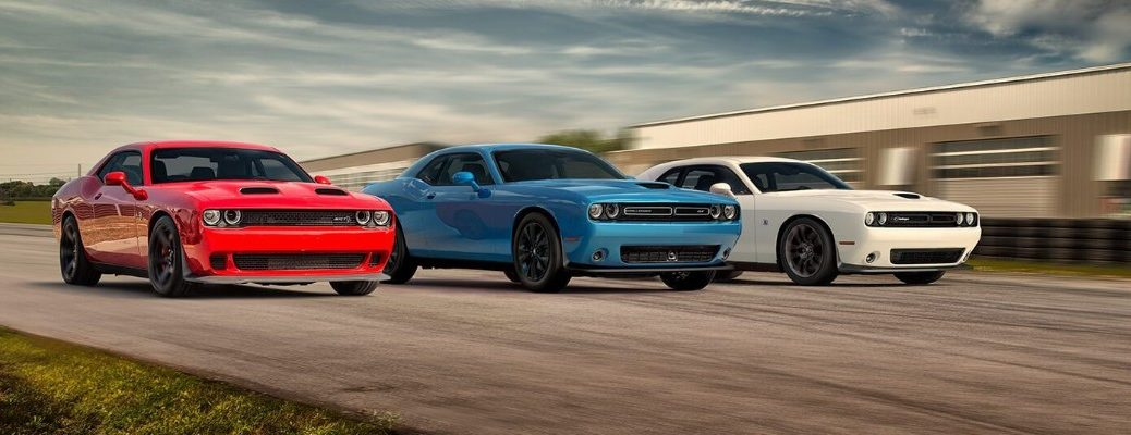 2020 Dodge Challenger models with different packages and trims in red, light blue, and white paint colors racing down a strip of road near grass and a concrete bridge
