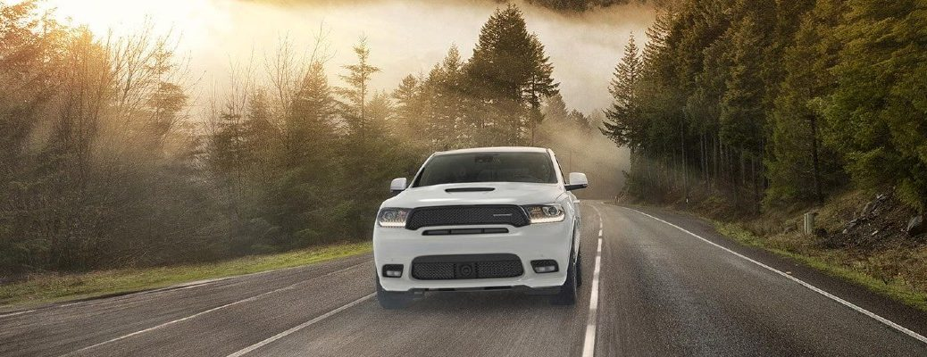 2020 Dodge Durango SRT white paint hood scoop on forest road with clouds and trees in background at sunset