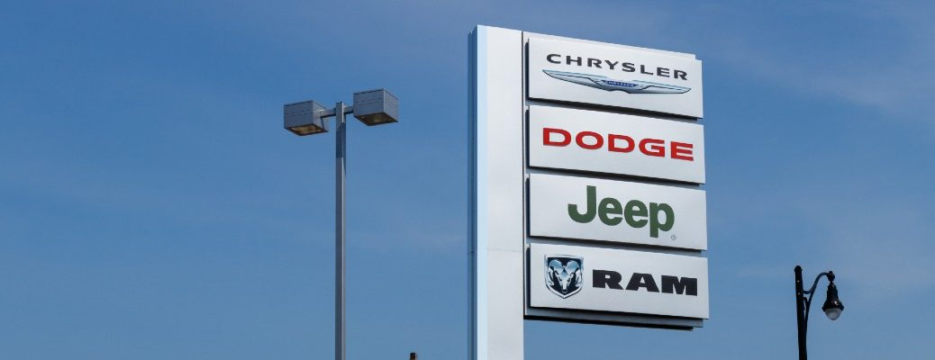 Chrysler Dodge Jeep and Ram dealership sign up in a blue sky near a streetlight