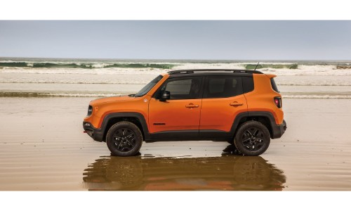 2019 Jeep Renegade exterior side shot orange paint job parked on a wet shallow beach